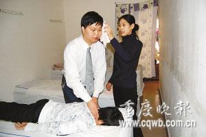 李建全给客人按摩,妻子给他擦汗。