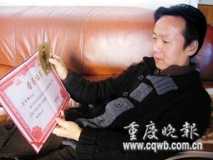 马吉相一手拿着荣誉证书,一手拿着儿子生前照片,神情忧伤。