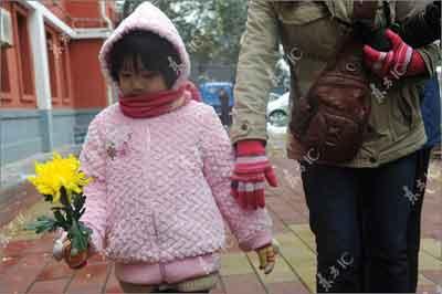 2009年11月1日,北京玉渊潭畔中国航天大院内钱学森家中布置灵堂,接受公众吊唁。一名小朋友在母亲带领下前来悼念。