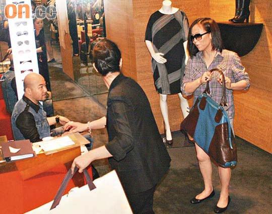 邓萃雯试好衣服当即付款,黄伟文则坐着等候。