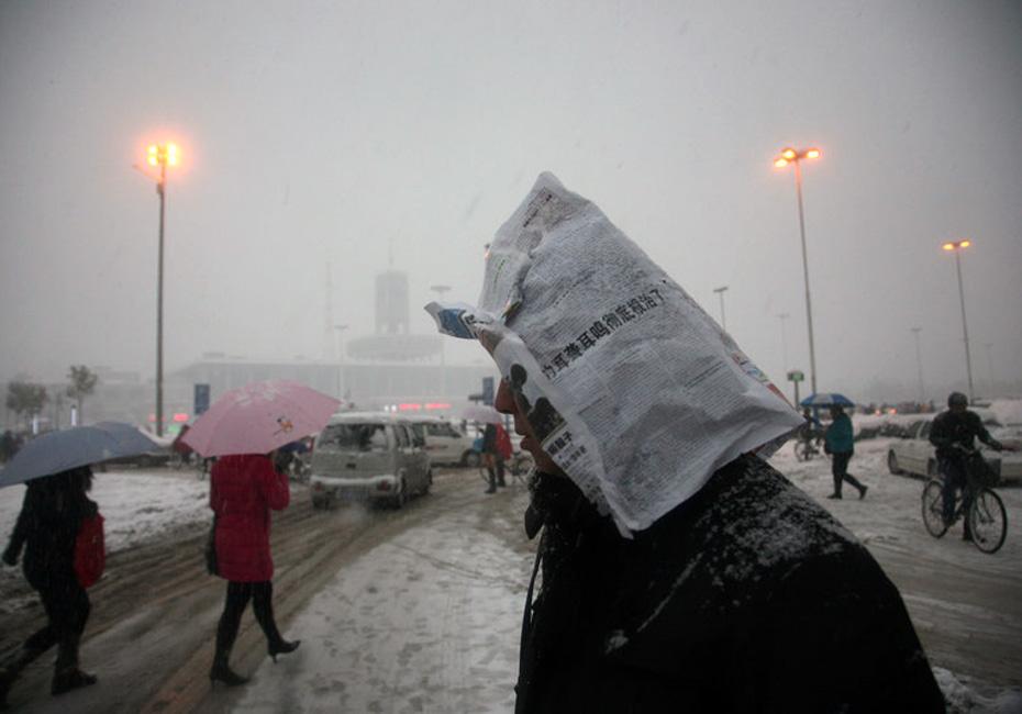 中国 大部地区/图为一位行人将报纸折成帽子挡雪。阿拉尔摄