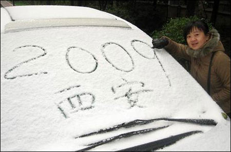 11月11日,在西安市皇城西路,一位市民在车玻璃上写字 (来源:新华网)