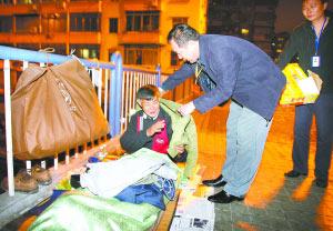 市民政局工作人员为天桥上的流浪者送上御寒衣物。