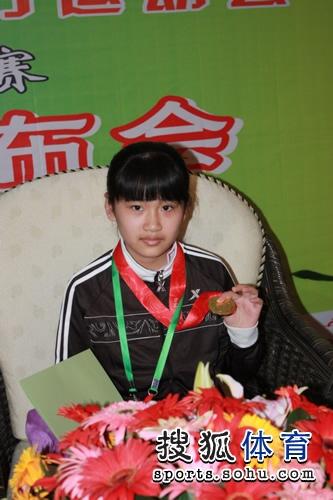 图文:围棋女子业余组颁奖 12岁於之莹展示金牌