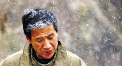 崂山北九水景区下起小雪,一名登山游玩的游客头发被雪花染白