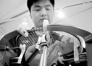 董俊峰正在给球拍穿线 摄/宫云捷