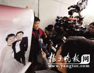 郑琳的父亲举着女儿女婿的婚纱照来到法院。范晓林 摄