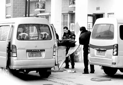 今天上午,民警将死者家的防盗门运走 摄/记者黑克
