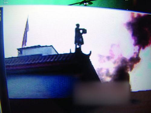唐福珍站在楼顶自泼汽油前的瞬间。(视频截图 来源:人民网)
