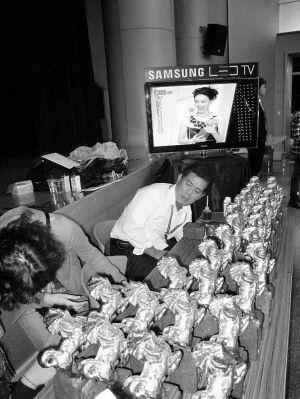 手工师傅(右)通过身后的电视观看直播,同时准备完成金马奖座的最后制作工序。