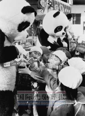 1980年2月6日晨,中国赠送的大熊猫欢欢抵达东京上野动物园。大熊猫人偶向前来观看欢欢的日本小朋友赠送小玩具。本报资料图