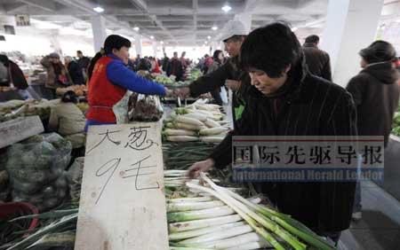 近日,北京市场上大葱的批发价平均为每斤9角,比去年同期上涨了2角多。图为北京一家菜市场。本报记者 李文/摄