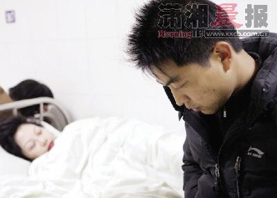 12月4日,长沙市中心医院,阿红躺在病床上,坐在一旁的丈夫王先生很后悔。图/记者 殷建军