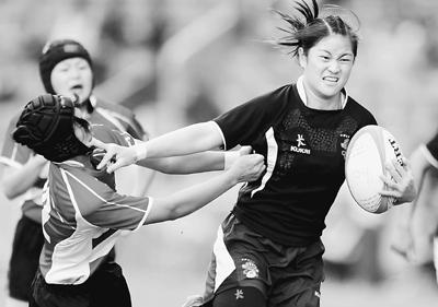 12月6日,在东亚运动会女子七人制橄榄球决赛中,中国队以34∶12战胜日本队,夺得冠军。图为中国队球员刘艳(右)在比赛中进攻。