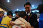 民政部王振耀司长为孤残儿童代表穿上爱心毛衣