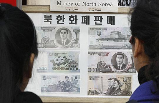 2月1日,韩国板门店一侧的韩国游客正在一块展板前看新出的朝鲜货币。