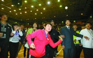 郭跃将签名的乒乓球打向看台,送给深大的同学们。