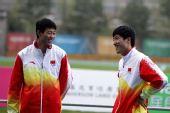 图文:刘翔获得男子110米栏冠军 与纪伟说笑