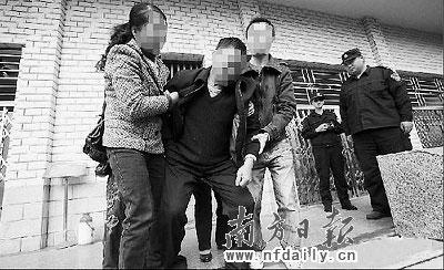 邢鲲的父亲在家人的搀扶下走出尸检室