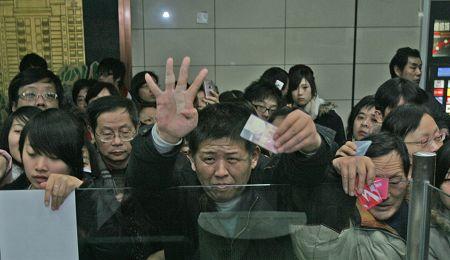 12月22日,轨交1号线中山北路车站内,一名乘客(中)在办理退票手续和领取致歉信时, 伸出4个手指头抱怨被困列车内长达4小时之久。早报见习记者 王浩然 图