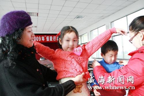 """12月21日,乳山市参与""""恒爱行动""""的爱心妈妈,将自己亲手编织的60件毛衣送到孤残儿童手中,让孩子们感受到母爱的温暖。图为爱心妈妈正在为孩子们穿上温暖漂亮的毛衣。(记者 赵平平 摄)"""