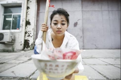 俞晴/图文:奥运天使沿街乞讨碗里惊现一百元