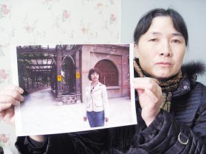 胡母拿着女儿的照片欲哭无泪。梅建明