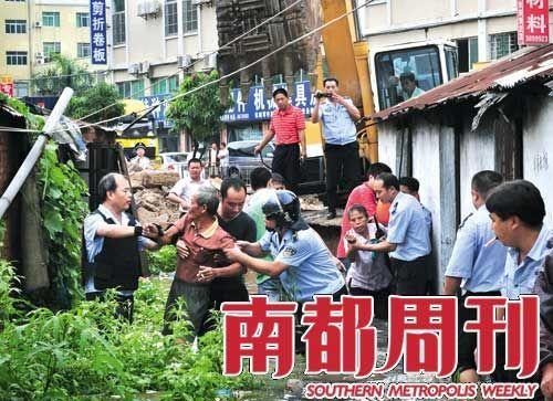 """2009年8月6日,台风""""天鹅""""刚过,珠海屏西路施工路段,拆迁队在水中把不愿意离开现场的村民强行拖离。 摄影_谭伟山"""
