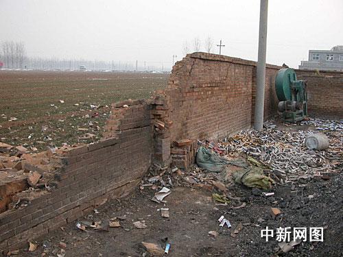 爆炸现场围墙被炸开数米缺口,爆竹筒散落一地。作