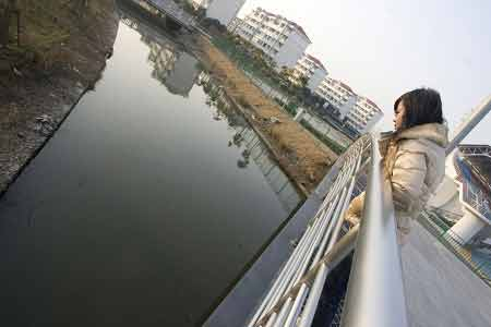昨天下午,一名女子望着事发的河流。两名大学生凌晨溺亡于此河。早报见习记者 王浩然 图