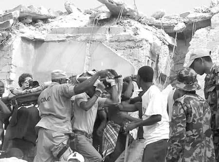 1月12日,在海地首都太子港,人们用担架抬走一名受伤者。 新华社发