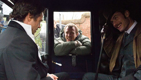 盖-里奇(中)在《福尔摩斯》片场给小罗伯特-唐尼(左)和裘德-洛(右)说戏