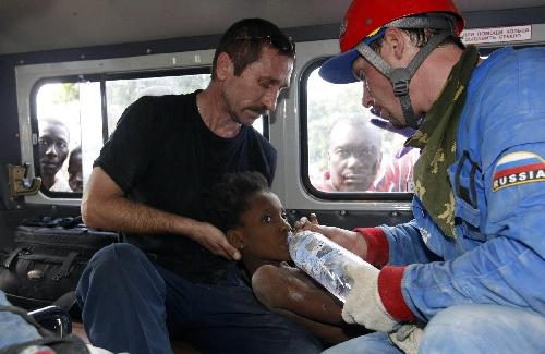 俄罗斯救援人员给刚被救出的儿童喂水。新华社/路透