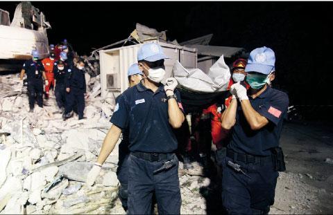 救援人员正在将我遇难同胞遗体抬出地震现场