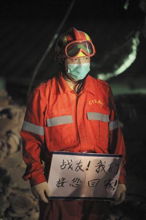 """一名中国国际救援队队员手持""""战友!我们接您回家!""""的标语送别遇难战友"""