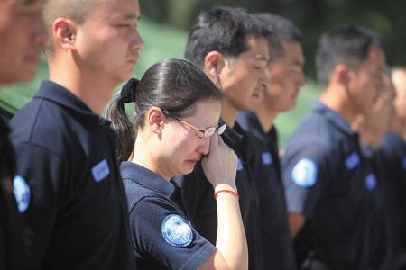 看到战友遗体被送回营地,一名女警忍不住垂下了眼泪