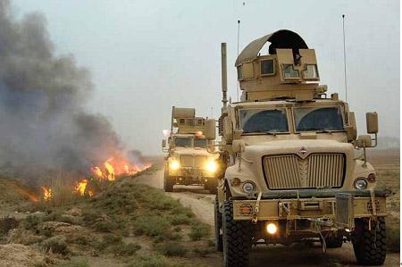 """驻伊拉克美军士兵在""""防地雷反伏击车""""中清查路边可能藏有""""自制爆炸装置""""的植被。"""