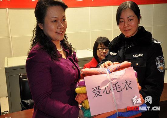 湖南省妇联主席肖百灵(左)接过由400余名服刑人员精心编织的649件爱心毛衣。
