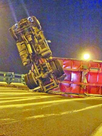 侧翻的半挂车堵塞了整条路面。