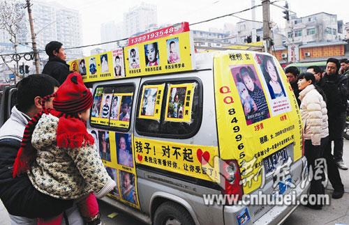 """这是一辆满载痛苦的车:牌照""""陕AFA027"""",银灰色解放牌面包车,车身上贴着55个被拐卖和失踪孩子的照片。"""