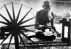甘地坐在纺车旁边读书的情景