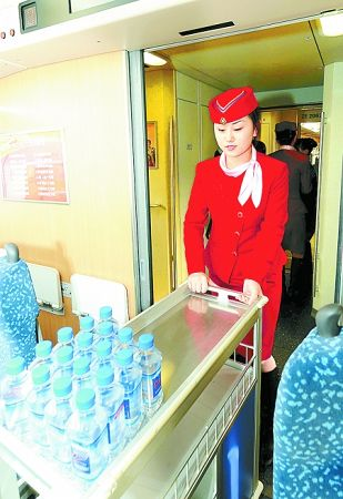 1月29日,乘务员在试运行的列车上准备饮用水。新华社发