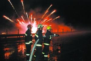 消防员灭火时,礼花仍不停燃起。通讯员 李林 摄
