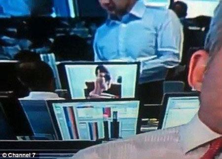 当一名同事走到他的电脑屏幕跟前与他说话时,这名男子依然继续看照片。
