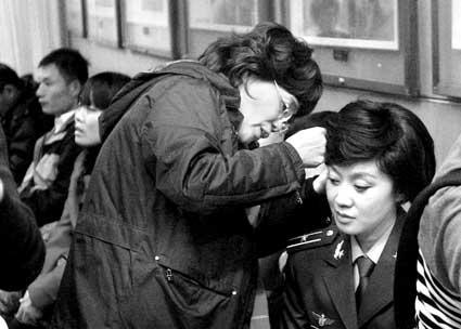 闫妮(右)上场前,化妆师为其整理发型。她将在小品中扮指导员
