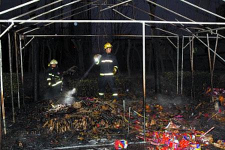烟花摊点被炸毁,消防队员在现场勘查。