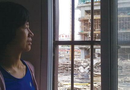 林书立的妹妹站在自己家的窗户旁,窗外就是在建的工地