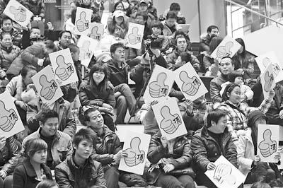 """2010年1月1日,""""山寨春晚""""发起人老孟,在北京soho尚都举办演员选秀活动,为今年的山寨春晚遴选节目。演出现场,观众手持牌子参与对每个节目的评判。吕家佐摄"""