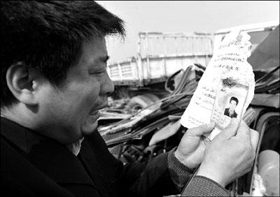 2月23日,孙东林看着从事故车残骸中找到的哥哥照片。新华社发