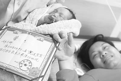 """2008年8月8日,在海口琼山妇产科医院,钟月卿开心陪护在她当日8时8分剖腹产下的""""奥运宝宝""""身边。"""